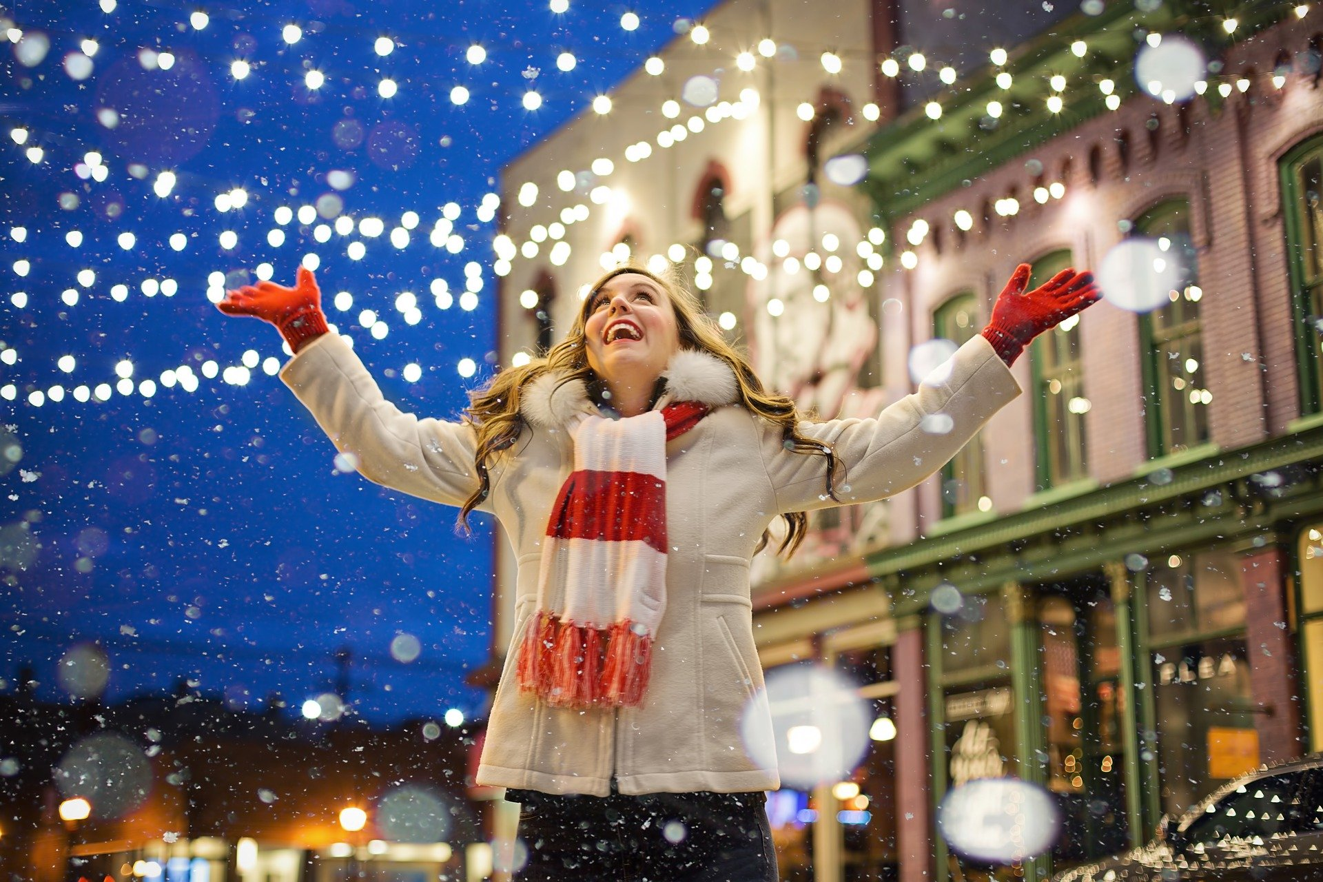 Woman raising her arms in the city during Christmas Holidays